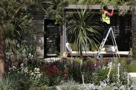 A worker prepares the Cancer Research UK Garden ahead of the opening of the Chelsea Flower Show 2011 on Tuesday, in London in this file photo taken May 22, 2011. REUTERS/Luke MacGregor