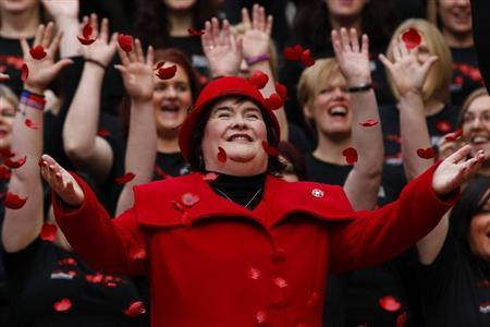Singer Susan Boyle smiles as poppy's fall over her at a photocall during the launch of the Poppy Scotland appeal in Glasgow, Scotland in this file photo taken October 24, 2012. REUTERS/David Moir