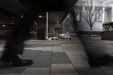A homeless person lies on a street as a passerby walks past in Tokyo February 27, 2013. REUTERS/Yuya Shino