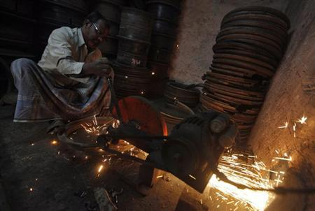 A worker repairs iron rings used in heavy wheels inside a small scale factory in Kolkata February 12, 2013. REUTERS/Rupak De Chowdhuri/Files