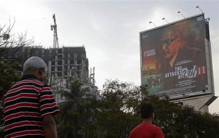 People walk underneath a promotional billboard for Ram Gopal Varma's film ''The Attacks of 26/11'' by a roadside in Mumbai February 28, 2013.REUTERS/Vivek Prakash