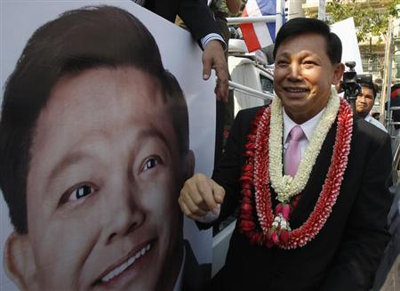 A candidate from the Pheu Thai Party, Pongsapat Pongcharoen, walks past his portrait after registering as a candidate for Bangkok governor at the Bangkok Metropolitan Administration January 21, 2013. . REUTERS/Chaiwat Subprasom