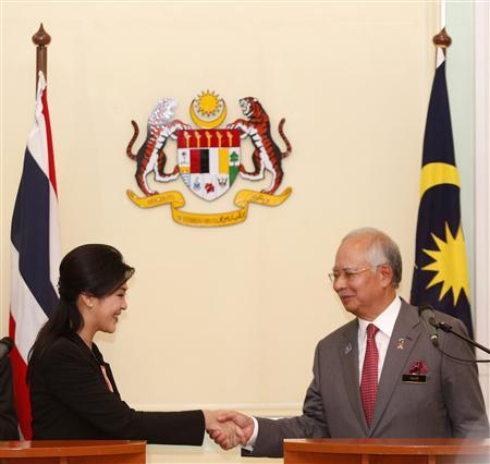 Visiting Thailand's Prime Minister Yingluck Shinawatra and her Malaysian counterpart Najib Razak shake hands at the end of their news conference at Razak's office in Putrajaya, outside Kuala Lumpur February 28, 2013. REUTERS/Bazuki Muhammad (