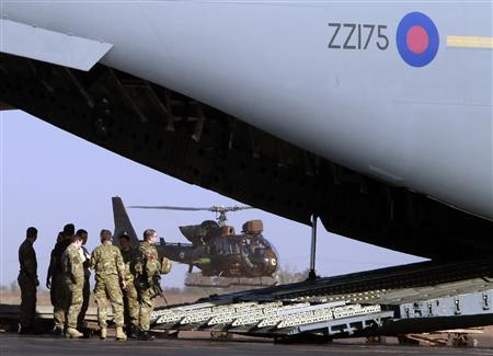 British soldiers unload a British C17 cargo aircraft while a French Gazelle helicopter takes off at the Mali air force base near Bamako January 18, 2013. REUTERS/Eric Gaillard