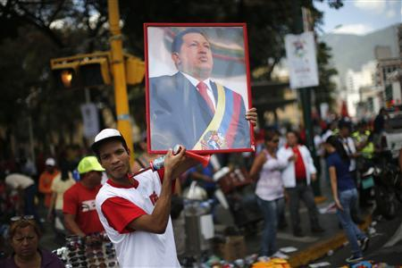 A supporter of Venezuela's President Hugo Chavez holds up a portrait of him while attending a rally in Caracas February 27, 2013. REUTERS/Jorge Silva