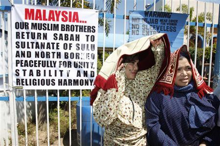 Followers of former Sultan of Sulu Jamalul Kiram III stand in front of a banner displayed at the gate of Blue Mosque in Maharlika village, Taguig city, south of Manila, March 1, 2013. REUTERS/Romeo Ranoco