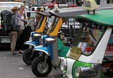 "Tourists ask a ""tuk tuk"" taxi driver for directions along Khao San Road in Bangkok July 13, 2012. REUTERS/Sukree Sukplang"