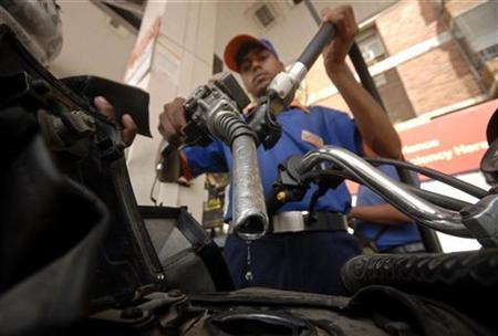 A worker holds a fuel nozzle at a petrol pump in Hyderabad June 17, 2010. REUTERS/Krishnendu Halder/Files