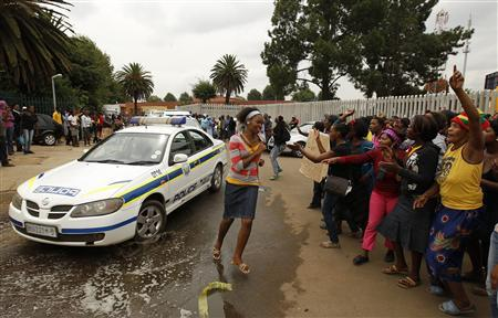 Protesters gesture as a police car drives past outside the Daveyton Police station east of Johannesburg, March 1, 2013. REUTERS/Siphiwe Sibeko