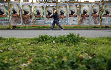 A man walks past posters supporting Cardinal Peter Turkson on boards in downtown Rome March 1, 2013. With Pope Benedict XVI now officially in retirement, Catholic cardinals from around the world begin on Friday the complex, cryptic and uncertain process of picking the next leader of the world's largest church. REUTERS/Alessandro Bianchi (ITALY - Tags: RELIGION)