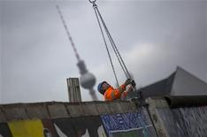 A worker attaches the clamp of a crane to a segment of the former Berlin Wall, now called the East Side Gallery, in Berlin March 1, 2013. REUTERS/Thomas Peter