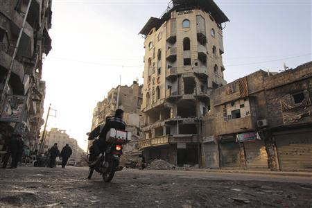 Men on a motorbike ride past the damaged al-Shifa hospital in Aleppo February 27, 2013. REUTERS/ Giath Taha