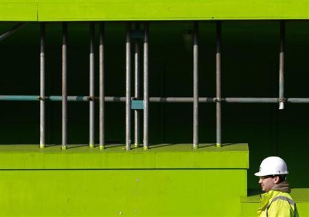 A construction worker walks in a building site in London March 2, 2011. REUTERS/Luke MacGregor