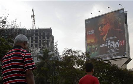 People walk underneath a promotional billboard for Ram Gopal Varma's film ''The Attacks of 26/11'' by a roadside in Mumbai February 28, 2013. REUTERS/Vivek Prakash