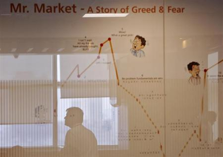A trader is reflected onto a glass panel with an illustration showing the nature of the stock market during the announcement of the annual budget at the Motilal Oswal trading floor in Mumbai February 28, 2013. REUTERS/Vivek Prakash