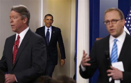 U.S. President Barack Obama walks into the press briefing room while television correspondents Major Garrett (L) and Jonathan Karl (R) are talking live on TV after a meeting with Congressional leaders in the Oval Office at the White House in Washington March 1, 2013. REUTERS/Larry Downing