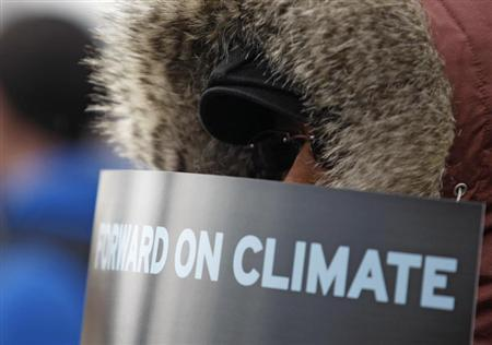 A demonstrator holds a sign during a march against the Keystone XL pipeline in Washington, February 17, 2013. REUTERS/Richard Clement