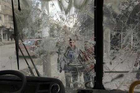 Boys are pictured through a broken windshield as they stand on a street in Aleppo February 28, 2013. REUTERS/ Giath Taha