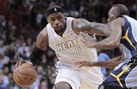 Miami Heat's LeBron James (L) dribbles against Memphis Grizzlies' Quincy Pondexter (R) in the first half of their NBA basketball game in Miami, Florida March 1, 2013. REUTERS/Andrew Innerarity