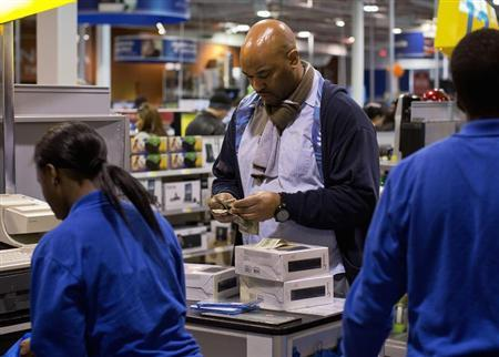 A man counts his money while making a purchase at the Best Buy electronics store in Westbury, New York November 23, 2012. REUTERS/Shannon Stapleton