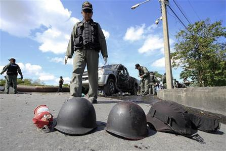 Security forces inspect the site of a bombing in Thailand's southern Yala province March 2, 2013. The motorcycle bomb explosion on Saturday killed two rangers and injured 13 other people in Thailand's troubled Yala province, police said. REUTERS/Surapan Boonthanom
