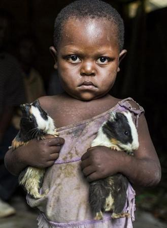 A girl poses for a photograph carrying two guinea pigs she was given during a distribution of the animals to her community as part of a food security program of Action Against Hunger International (ACF) in Karete February 19, 2013. REUTERS/Jana Asenbrennerova