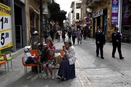 Two Cypriot policewomen patrol at a main market street of capital Nicosia February 25, 2013. REUTERS/Yorgos Karahalis