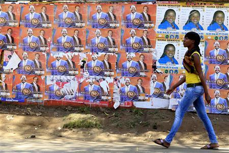 A woman walks past election campaign posters with the image of Kenya's Prime Minister Raila Odinga, the presidential candidate of the Coalition for Reforms and Democracy (CORD) and his running mate Kalonzo Musyoka in Kibera slum in the capital Nairobi February 28, 2013. REUTERS/Noor Khamis