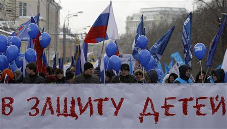 People march during a rally in support of a ban on U.S. adoptions in Moscow, March 2, 2013. Demonstrators walked along Moscow streets to support the new law prohibiting the adoption of Russian children by Americans and to commemorate the adopted Russian-born children who later died in the United States, according to participants. The banner reads, ''In defence of children''. REUTERS/Maxim Shemetov