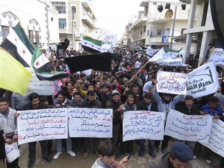 Demonstrators carry banners and wave flags during a protest against Syria's President Bashar al-Assad in Binnish in Idlib province, March 1, 2013. REUTERS/Mohamed Kaddoor/Shaam News Network/Handout