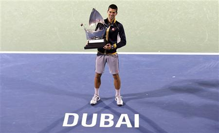 Novak Djokovic of Serbia poses with the trophy after winning his men's singles final match against Tomas Berdych of Czech Republic during the ATP Dubai Tennis Championships, March 2, 2013. REUTERS/Ahmed Jadallah
