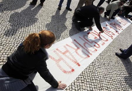 People paint a banner before the start of a march against government austerity policies in Lisbon March 2, 2013. REUTERS/Jose Manuel Ribeiro