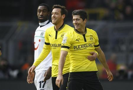 Borussia Dortmund's Julian Schieber (C) and Robert Lewandowski celebrate a goal, while Hannover 96's Joahn Djourou (L) looks on during the German first division Bundesliga soccer match in Dortmund March 2, 2013. REUTERS/Ina Fassbender