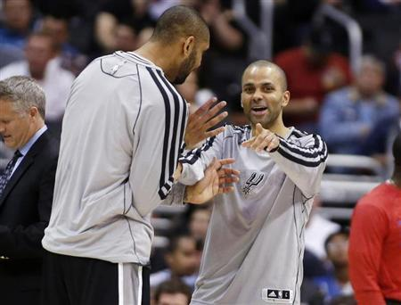 San Antonio Spurs' Tony Parker (R), of France, and Tim Duncan share a laugh against the Los Angeles Clippers during the second half of an NBA basketball game in Los Angeles February 21, 2013. REUTERS/Danny Moloshok