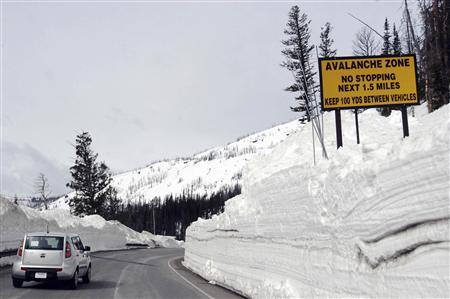 A car travels the newly plowed east entrance road over Sylvan Pass in Yellowstone National Park shortly after the park opened in this photo taken in May 2011. REUTERS/Ruffin Prevost