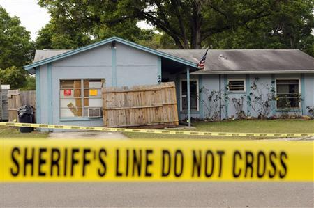 Police tape surrounds a home where a sinkhole opened up and swallowed a man in Seffner, Florida, March 1, 2013. REUTERS/Brian Blanco