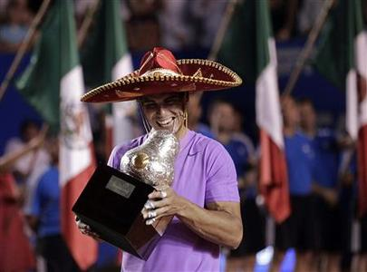 Rafael Nadal of Spain wearing a sombrero, a traditional Mexican hat, poses with his trophy after defeating compatriot David Ferrer during their men's singles final match at the Acapulco International tennis tournament in Acapulco March 2, 2013. REUTERS/Henry Romero