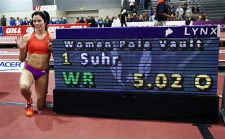 Jenn Suhr poses next to the score board after setting a new women's indoor pole vault world record of 5.02 metres (16 feet 5 1/2 inches) at the USA Indoor Track and Field Championships in Albuquerque, New Mexico March 2, 2013. The 31-year-old American's stunning vault on the first attempt at the height, eclipsed the previous indoor mark of 5.01m set by Russian great Yelena Isinbayeva in 2012. REUTERS/Eric Draper