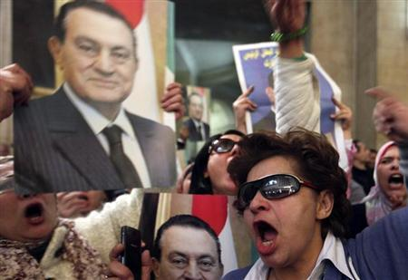 Supporters of deposed Egyptian president Hosni Mubarak celebrate and shout slogans while carrying a poster of him outside a High Court in Cairo January 13, 2013. REUTERS/Mohamed Abd El Ghany/Files