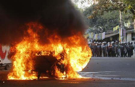 A vehicle burns in front of the police after activists from Bangladesh Nationalist Party (BNP) set fire to it during a clash in Dhaka March 2, 2013. REUTERS/Andrew Biraj