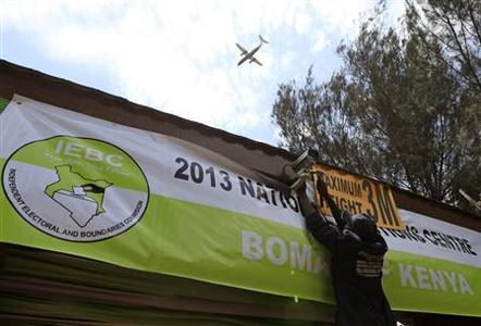 A man puts up a banner as a plane flies by in front of Kenya's national election centre in Nairobi March 3, 2013. Kenya will hold its presidential and parliamentary elections on March 4. REUTERS/Noor Khamis