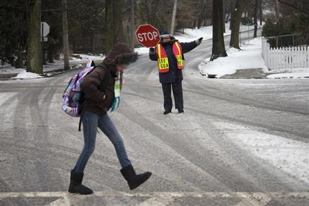 A guard helps a student cross an intersection in Pelham, New York February 8, 2013. REUTERS/Adrees Latif