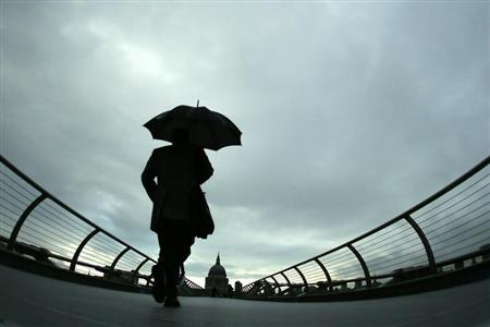Commuters cross the Millennium Bridge during a rainy morning, towards the financial district the City of London November 27, 2012. In background is St Paul's Cathedral. REUTERS/Stefan Wermuth
