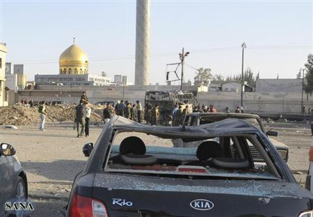 Security and residents inspect the site where a car bomb exploded in front of the gold-domed Shi'ite shrine of Sayyida Zeinab in southern Damascus, June 14, 2012. REUTERS/Sana/Handout
