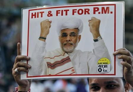 A supporter of the Bharatiya Janata Party (BJP) holds a poster featuring Narendra Modi during a jubilation ceremony outside the party office in Ahmedabad, December 20, 2012. REUTERS/Amit Dave/Files