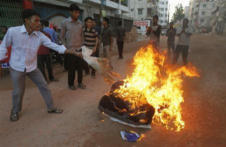 Activists from Bangladesh's Jamaat-e-Islami set fire to a pile of cotton material on a street during the first day of a two-day-long strike to protest against the decision by the country's war crimes tribunal to deliver judgement in the cases involving their top leaders in Dhaka March 3, 2013. REUTERS/Andrew Biraj