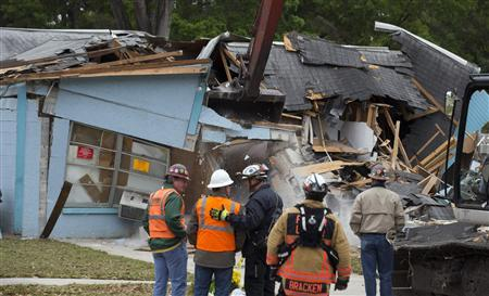 Demolition crews and Hillsborough County Fire Department watch as the house, where Jeffrey Bush was swallowed by a sinkhole, is demolished in Seffner, Florida March 3, 2013. REUTERS/Scott Audette