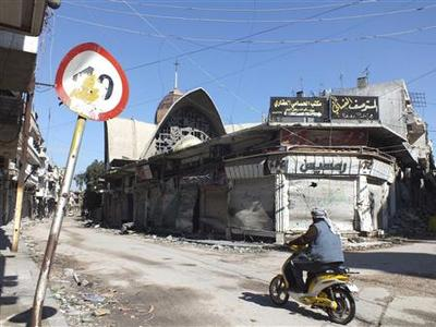A man rides a motorcycle through the old city of Homs March 2, 2013. REUTERS/Yazen Homsy