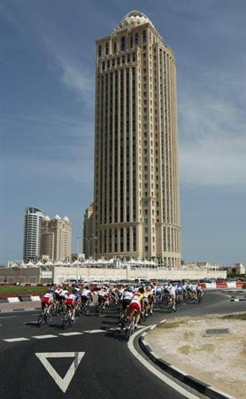 Cyclists cycle past the Qatar Telecom building in Doha February 3, 2010. REUTERS/ Fadi Al-Assaad