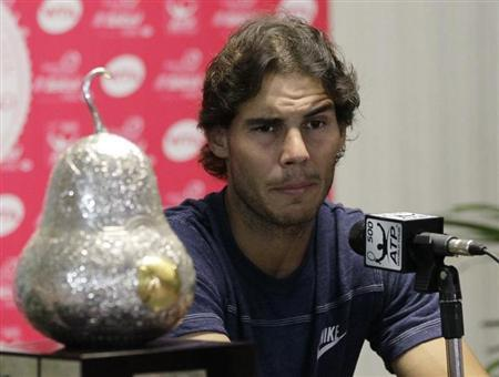 Rafael Nadal of Spain speaks beside the trophy during a news conference after winning his men's singles final match against his compatriot David Ferrer at the Acapulco International tennis tournament in Acapulco March 3, 2013. REUTERS/Henry Romero
